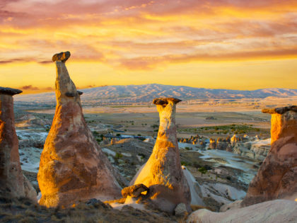 Rocks looking like mushrooms dramatically lit by a sunset in Cappadocia
