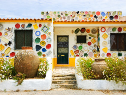 ALGARVE, PORTUGAL - MAY 3, 2015 Traditional colorful ceramic plates on the wall of the local pottery shop. Algarve is famous for its hand-painted pottery and ceramics.