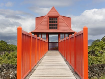 Red wooden viewpoint pathway in Pico island vineyard. Azores. Portugal. Horizontal